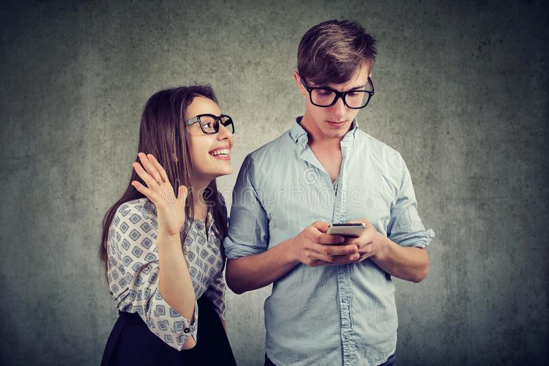 Kobieta próbuje przynosić uwagę przystojny mężczyzna ignoruje ona używa smartphone obrazy stock