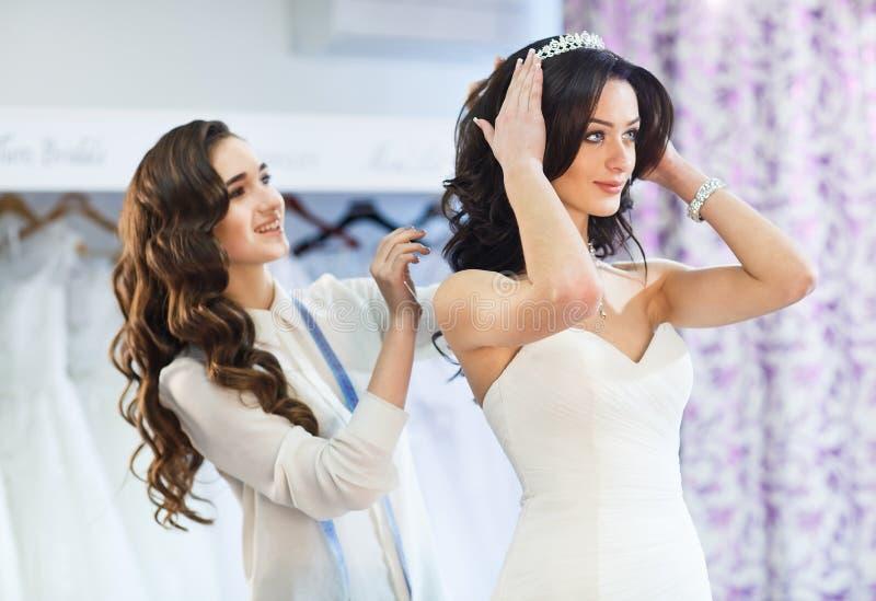 Kobieta pr?buje na ?lubnej sukni w sklepie z kobietami pomocniczymi obrazy stock