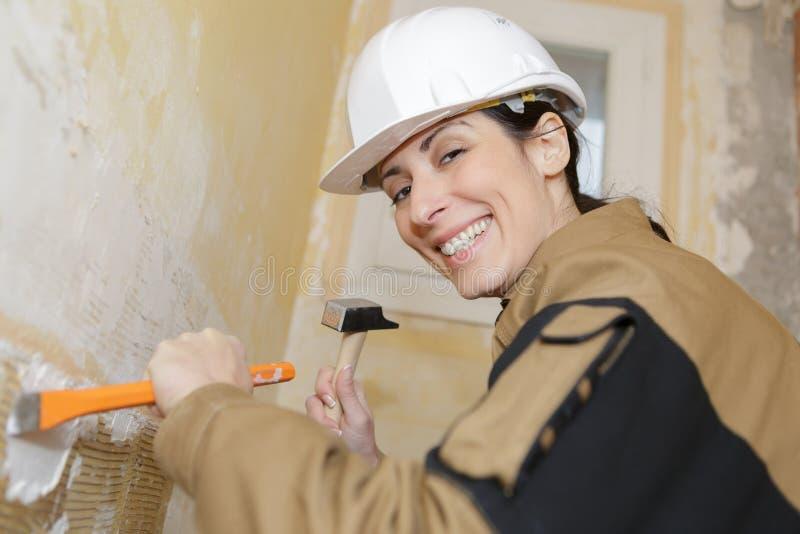 Kobieta pracownik budowlany szczerbi się oddalonego tynk obrazy stock