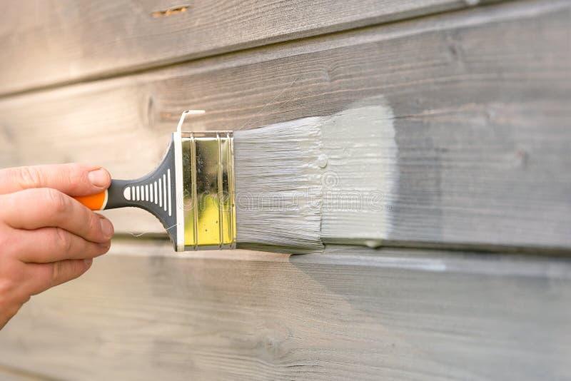 Kobieta pracownik maluje drewnianą domową zewnętrzną ścianę z paintbrush i drewnianym ochronnym kolorem obraz royalty free