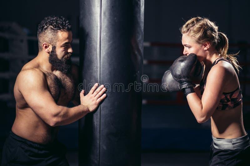 Kobieta pracująca z bokserskimi rękawiczkami i uderzać pięścią torbą z jej trenerem out obraz stock