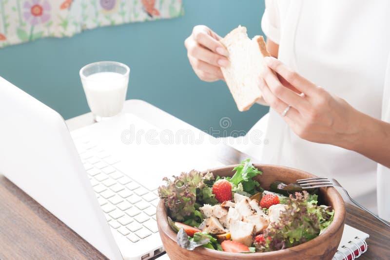 Kobieta pracująca z ranku posiłkiem, Selekcyjna ostrość na sałatce i wo, zdjęcie royalty free