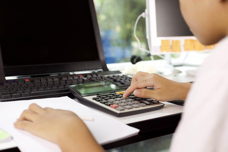 Kobieta pracuje na kalkulatorze zdjęcie stock