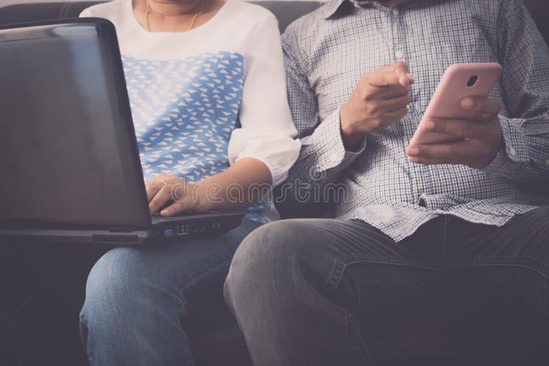 Kobieta pracuje na laptopie i mężczyzna używa telefon komórkowego oba siedzimy wpólnie na kanapie obrazy stock