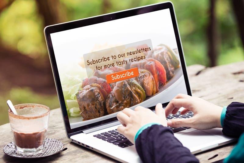 Kobieta pracuje na laptopie, komputerze robi/, prenumeruje karmowego blog na ekranie obraz stock