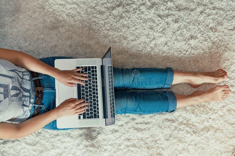 Kobieta pracuje na laptopie, online shoping, zapłata Kobieta używa laptopu obsiadanie na podłodze, gmeranie sieć, wyszukuje infor zdjęcia stock