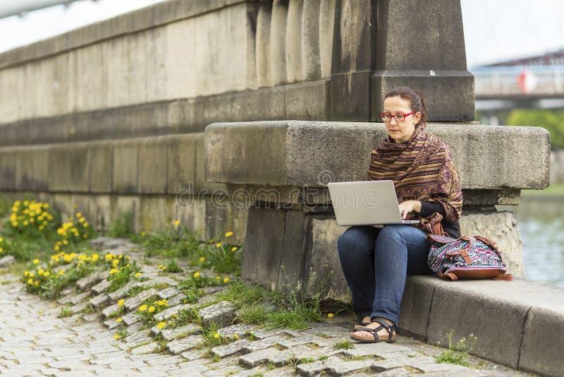 Kobieta pracuje na laptopie podczas gdy siedzący blisko rzecznego deptaka w starym miasteczku obraz royalty free