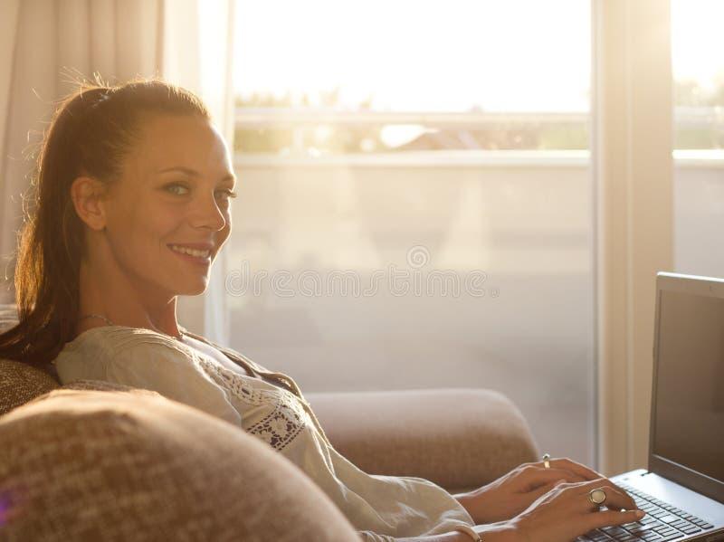 Kobieta pracuje na laptopie w żywym pokoju obraz royalty free