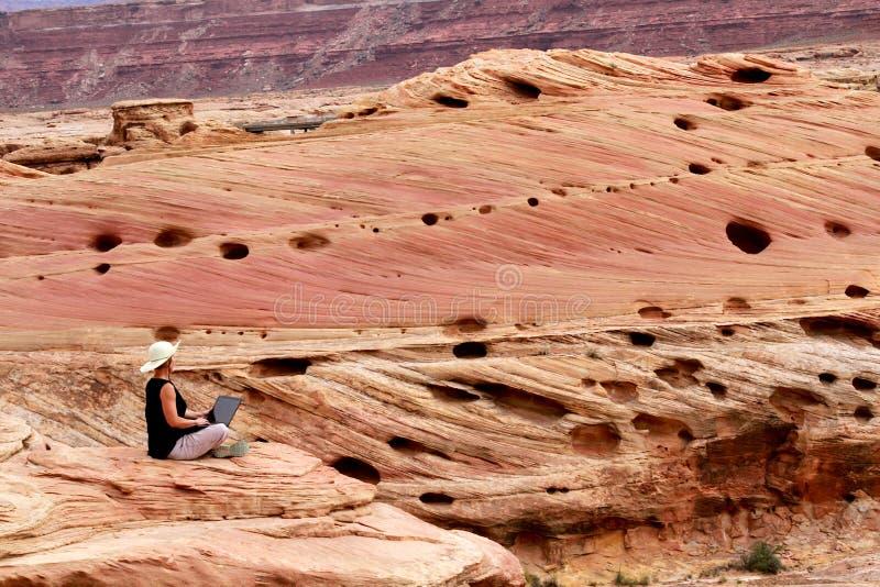 Kobieta pracuje na laptopie wysokim w górę skał na obrazy royalty free