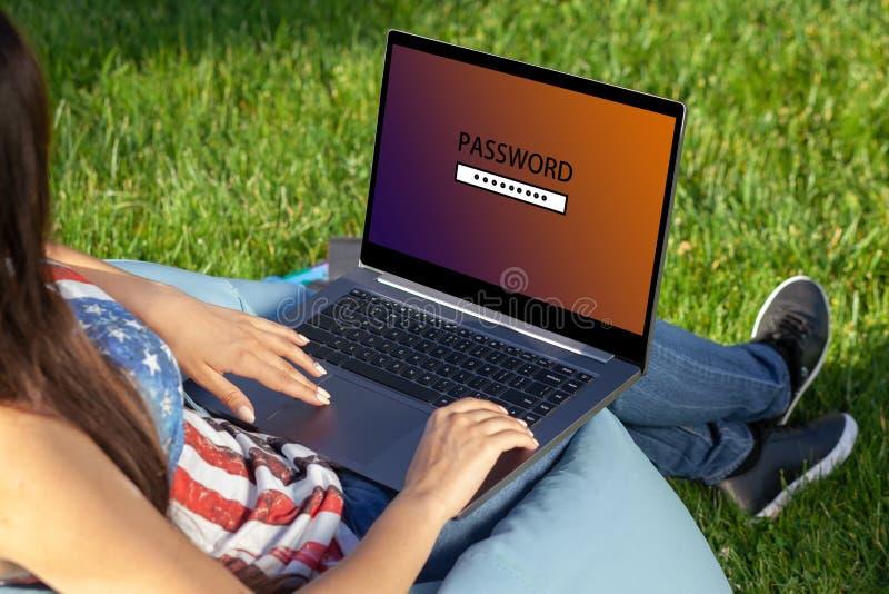 Kobieta pracuje na laptopu komputeru osobistego komputerze z prośby hasłem na ekranie, siedzi w parku na zielonej trawy światła s obrazy royalty free