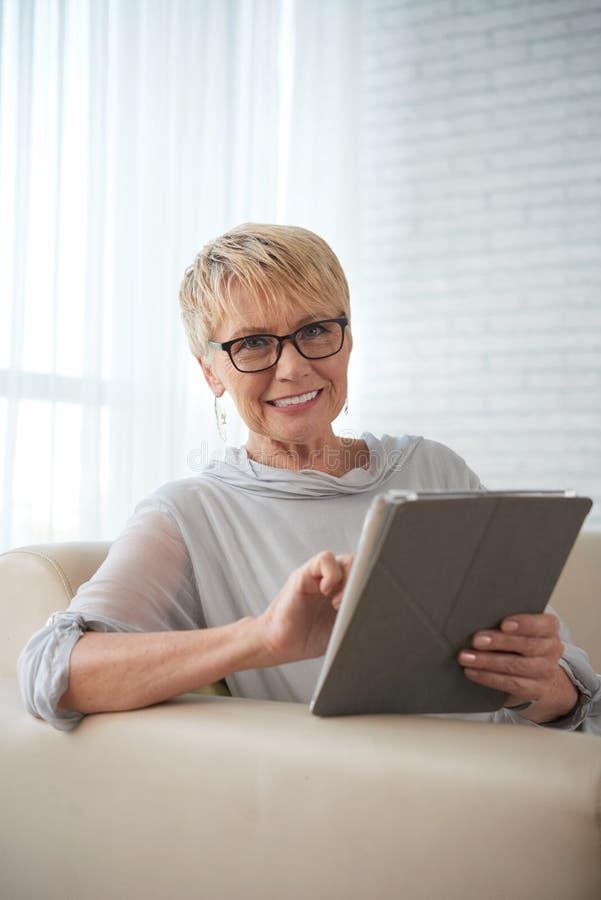 Kobieta pracuje online na pastylka komputerze osobistym obrazy stock