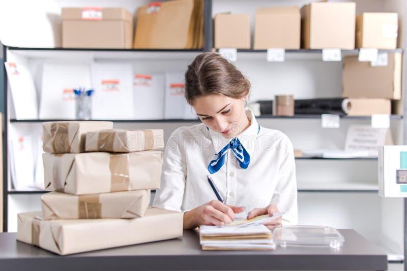 Kobieta pracuje przy urzędem pocztowym fotografia royalty free