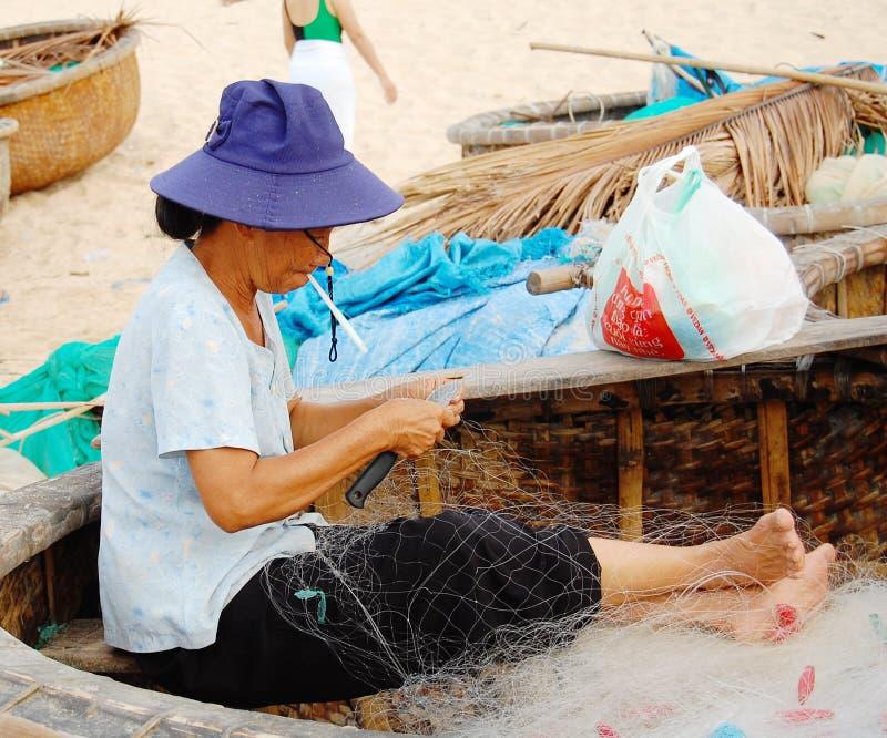 Kobieta pracuje z sieciami rybackimi na plaży w Phan Thiet, Wietnam obraz stock