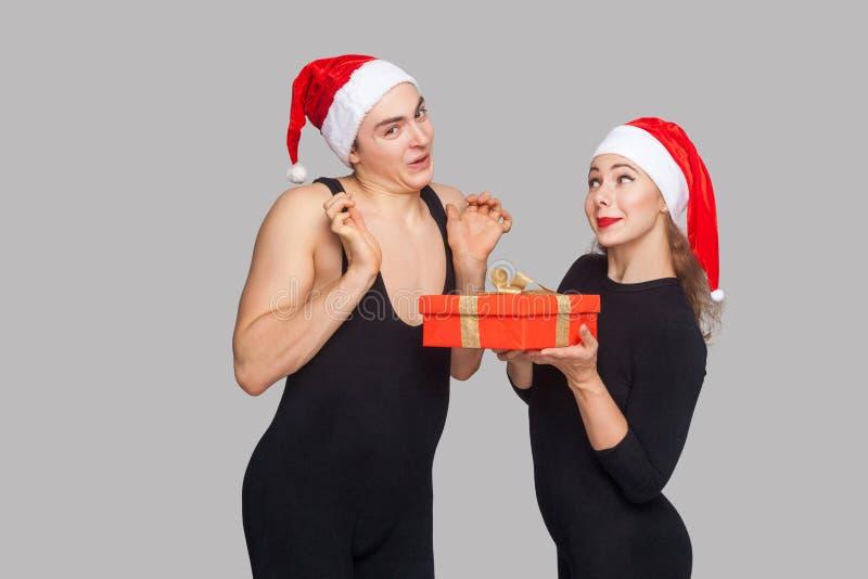 Kobieta prezenta pudełka teraźniejszy mężczyzna w Santa kapeluszu mężczyzna z nastroszonym ręki lo fotografia royalty free