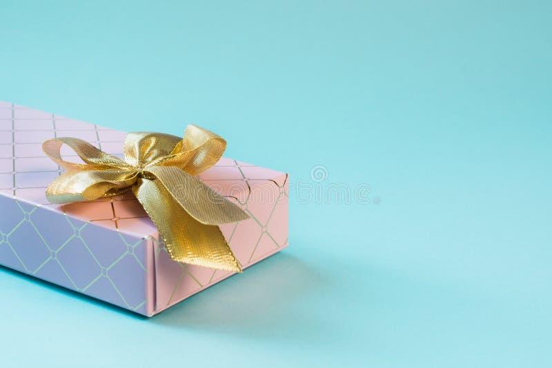 Kobieta prezenta różowy pudełko z złotym faborkiem na punchy pastelowym błękicie Urodziny kosmos kopii obraz stock