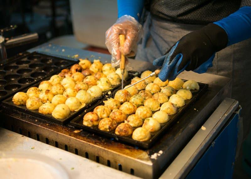 Kobieta proces gotować takoyaki przy nocy maket ja najwięcej popula zdjęcia stock