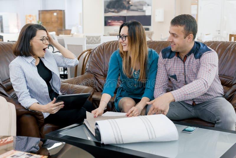 Kobieta projektanta zasłona pracuje z klient młodą rodziną wybiera tkaniny ich nowy dom zdjęcie royalty free