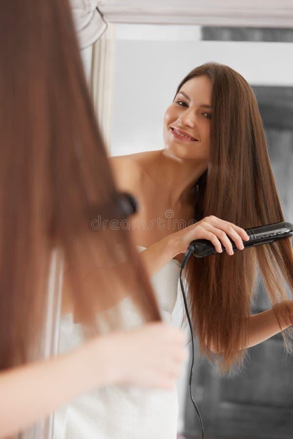 Kobieta prostuje włosy z prostownicą obraz stock