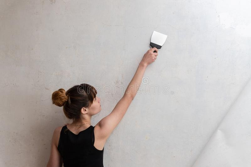 Kobieta prowadzi szpachelkę na betonowej ścianie zdjęcia stock