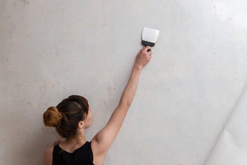 Kobieta prowadzi szpachelkę na betonowej ścianie Odświeżanie mieszkanie obraz royalty free