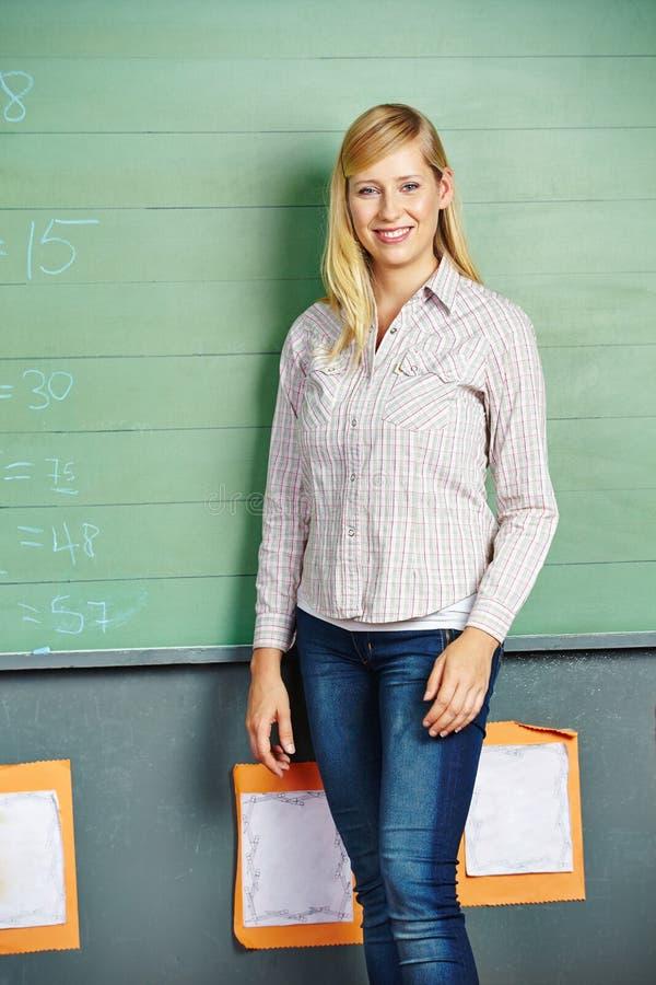 Kobieta przed chalkboard w szkole zdjęcia stock