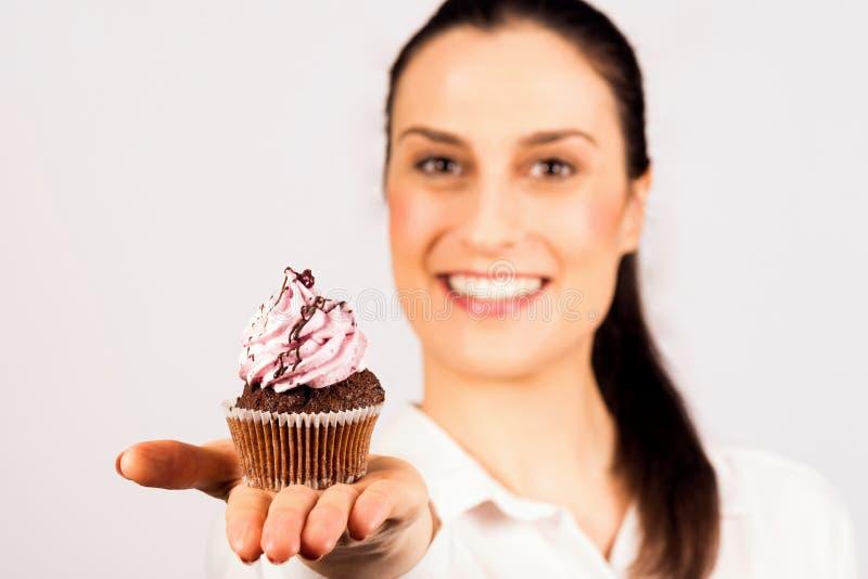 Kobieta przedstawia słodką babeczkę zdjęcie royalty free