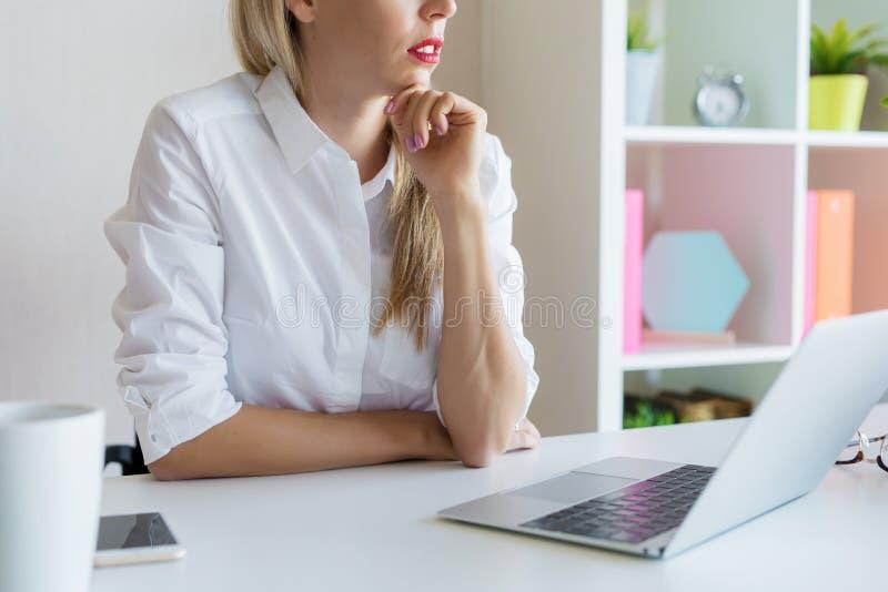 Kobieta przy biurowym obsiadaniem przy jej koncentrować i biurkiem zdjęcie royalty free