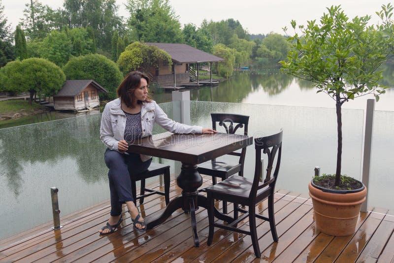 Kobieta przy cukiernianym stołem stawem zdjęcie royalty free