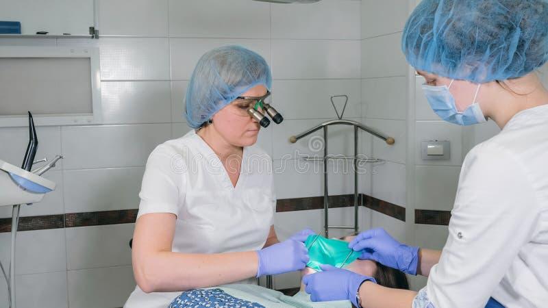 Kobieta przy dentysta kliniką dostają stomatologicznego traktowanie wypełniać zagłębienie w zębie Stomatologiczny przywrócenie i  zdjęcie royalty free