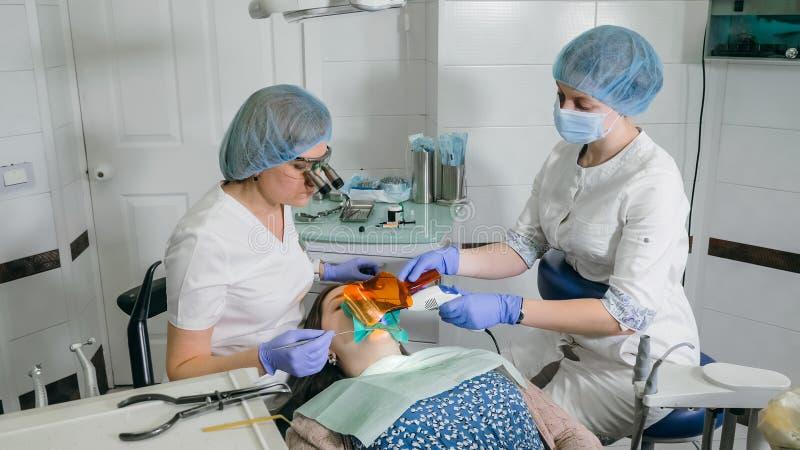 Kobieta przy dentysta kliniką dostają stomatologicznego traktowanie wypełniać zagłębienie w zębie Stomatologiczny przywrócenie i  fotografia royalty free