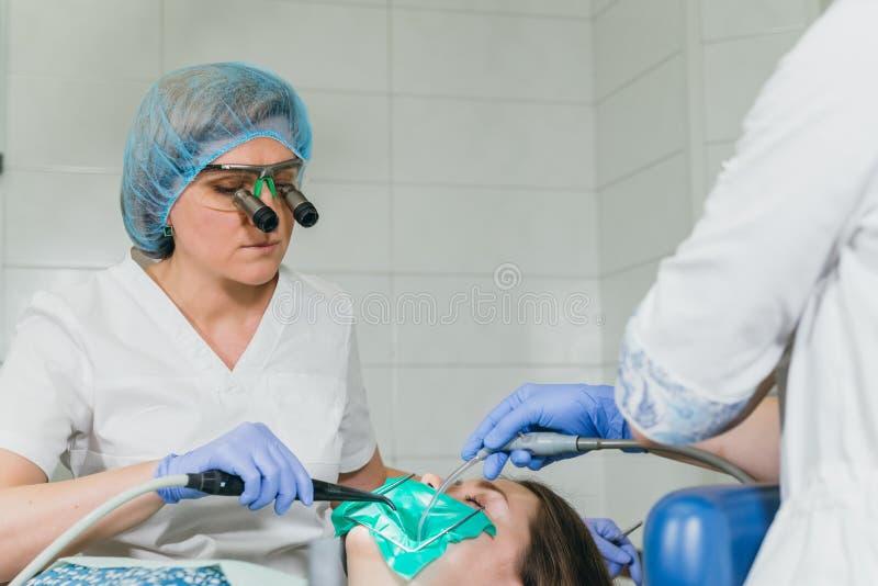 Kobieta przy dentysta kliniką dostają stomatologicznego traktowanie wypełniać zagłębienie w zębie Stomatologiczny przywrócenie i  obrazy royalty free