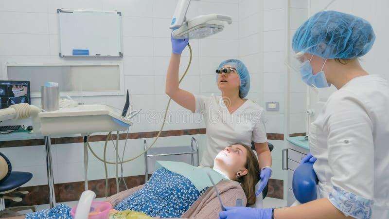 Kobieta przy dentysta kliniką dostają stomatologicznego traktowanie wypełniać zagłębienie w zębie Stomatologiczny przywrócenie i  obraz stock