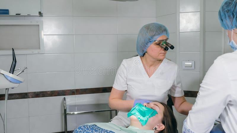 Kobieta przy dentysta kliniką dostają stomatologicznego traktowanie wypełniać zagłębienie w zębie Stomatologiczny przywrócenie i  zdjęcia royalty free