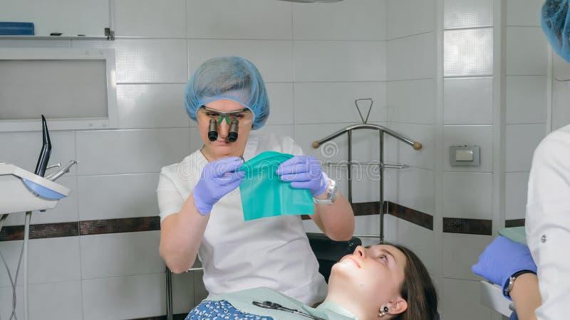 Kobieta przy dentysta kliniką dostają stomatologicznego traktowanie wypełniać zagłębienie w zębie Stomatologiczny przywrócenie i  fotografia stock