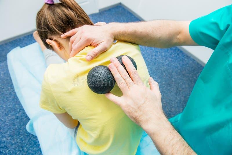 Kobieta przy fizjoterapia odbiorczym balowym masażem od terapeuta A kręgarza taktuje cierpliwego ` s thoracic kręgosłup w medyczn obrazy royalty free