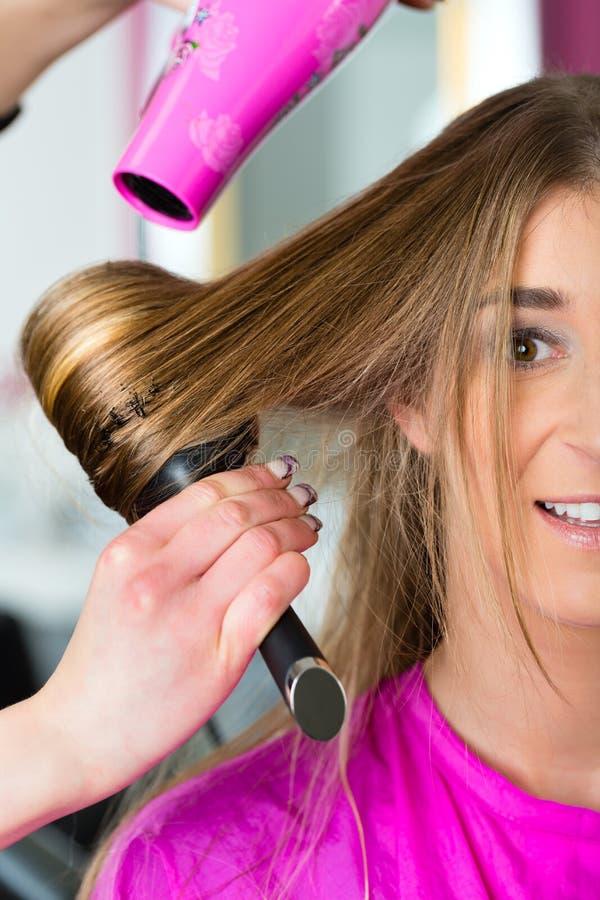 Kobieta przy fryzjerem ma włosy suszącego obrazy stock