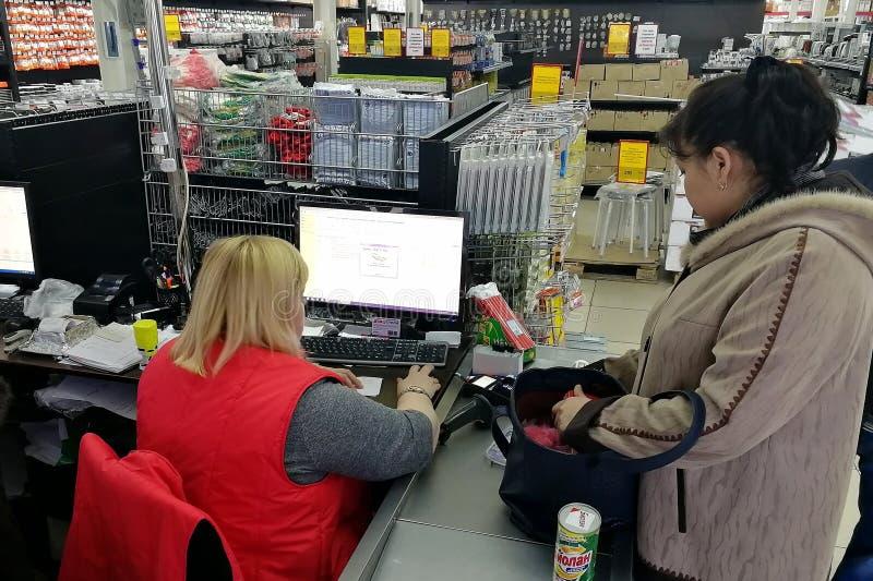 Kobieta przy kasą kupuje towary Sprzedawca uderza pięścią spojrzenia przy śmiertelnie i towary obraz stock