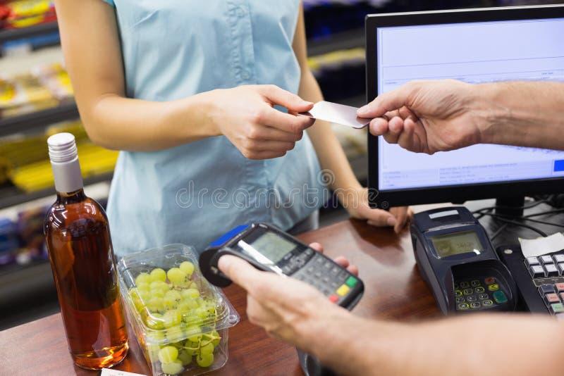 Kobieta przy kasą płaci z kredytową kartą fotografia royalty free