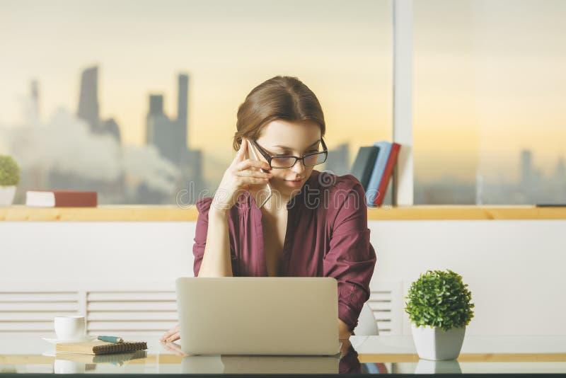 Kobieta przy miejscem pracy na telefonie fotografia royalty free