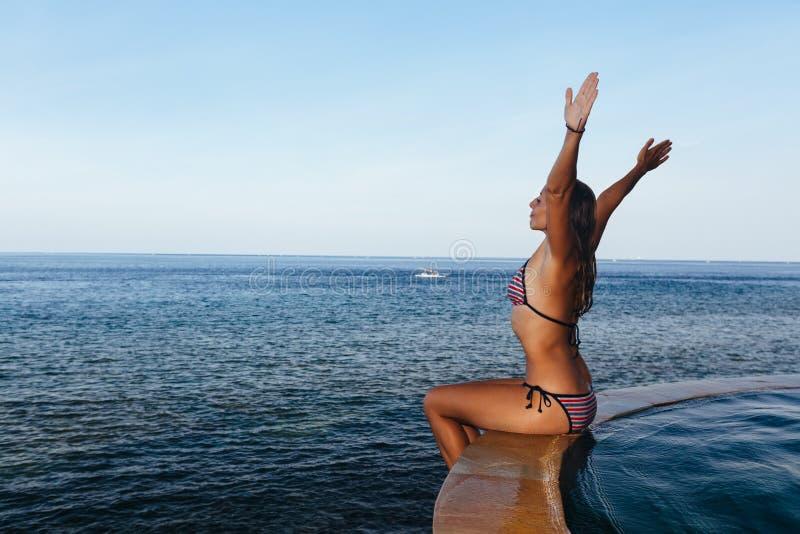 Kobieta przy nieskończoność pływackim basenem z dennym widokiem zdjęcia stock
