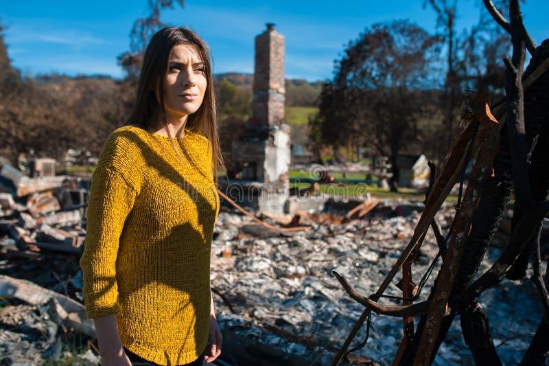 Kobieta przy palącym rujnującym jardem po pożarniczej katastrofy i domem, obrazy stock