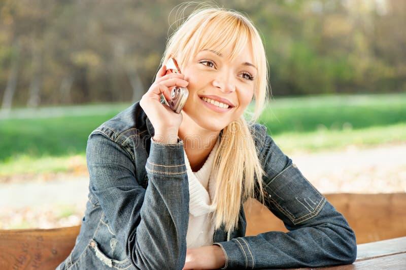 Kobieta przy parkiem bierze rozmowa telefonicza obraz stock