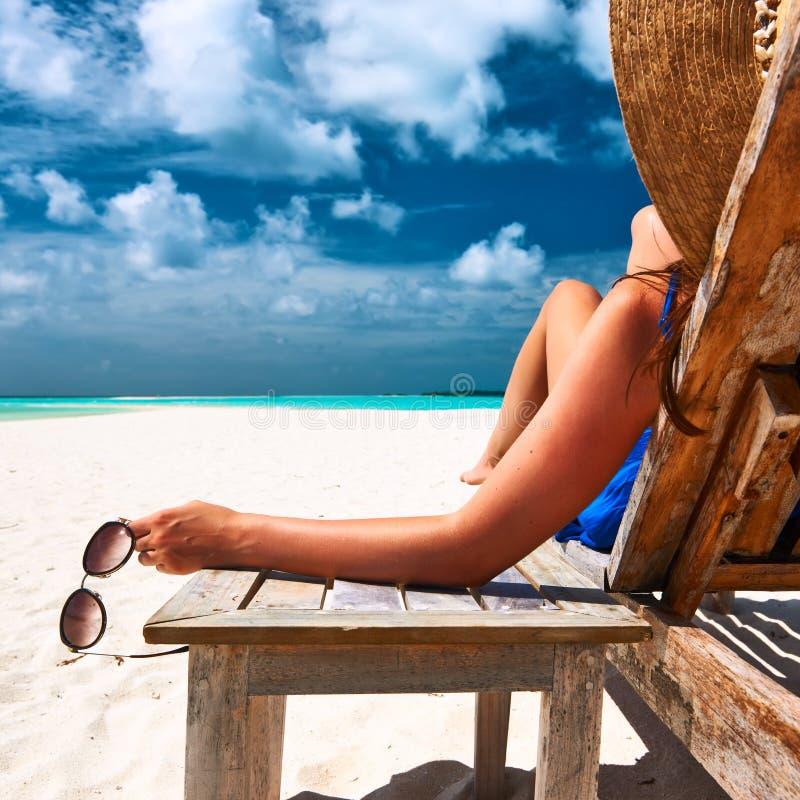 Kobieta przy plażowymi mienie okularami przeciwsłonecznymi zdjęcia stock