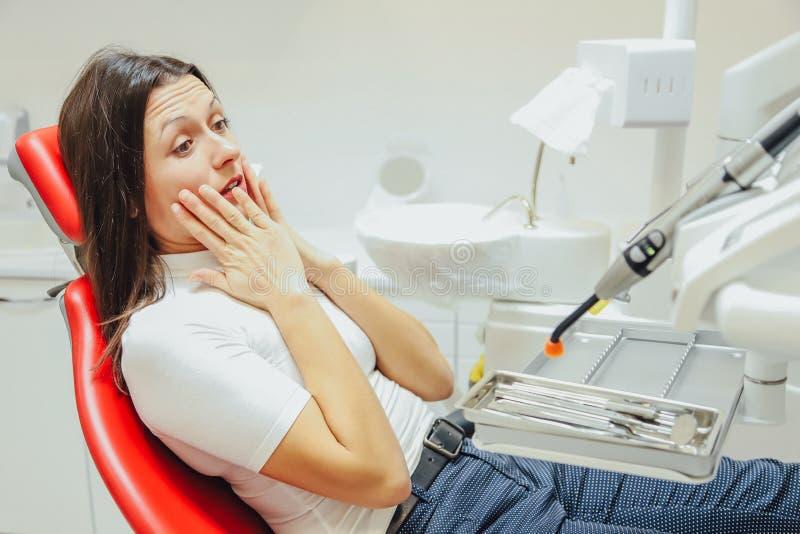 Kobieta przy przyjęciem dentysta w stomatologicznej klinice Siedzi w czerwonym krześle Z strachem pacjent patrzeje w zdjęcie stock
