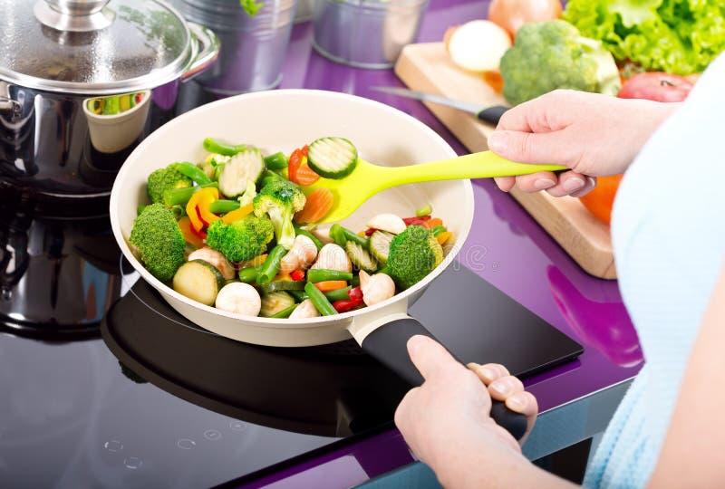 Kobieta przygotowywa smażących warzywa zdjęcie stock