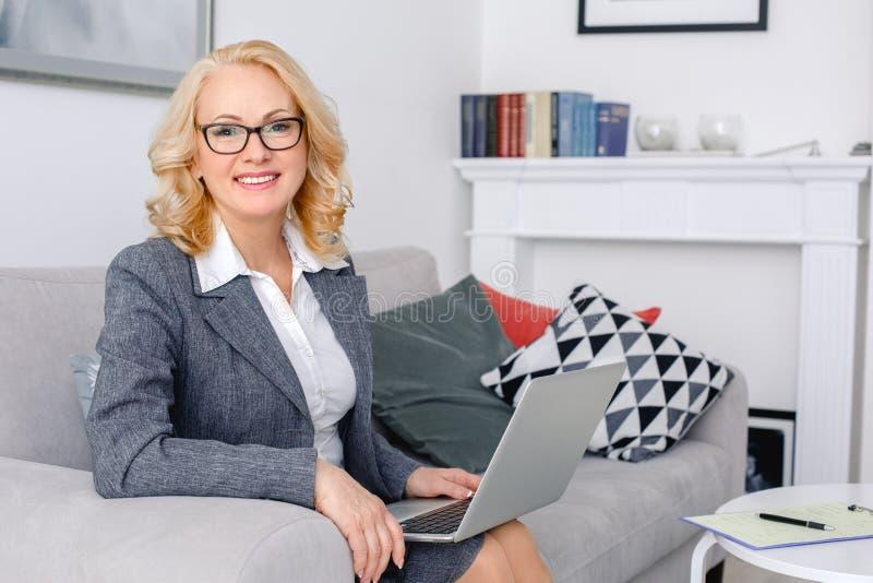 Kobieta psychologa portreta obsiadanie przy przypadkowym ministerstwa spraw wewnętrznych mienia laptopem obrazy royalty free