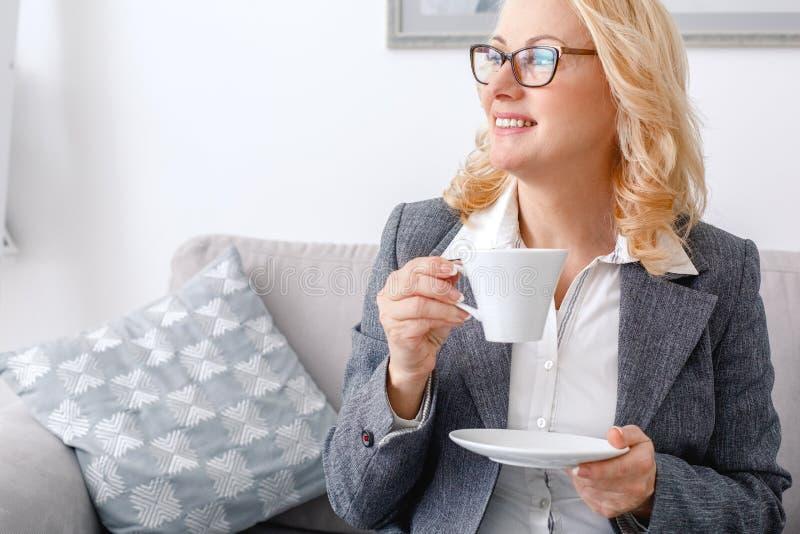Kobieta psychologa portreta obsiadanie przy przypadkowym ministerstwem spraw wewnętrznych pije gorącą kawę zdjęcie royalty free