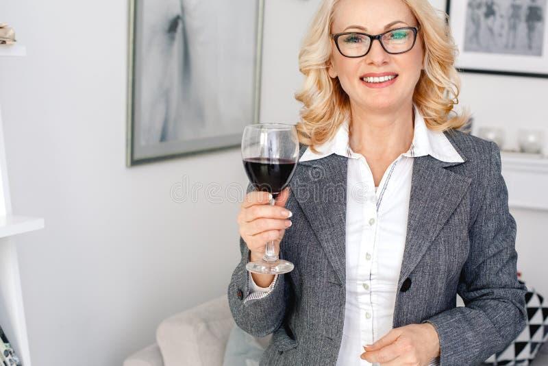 Kobieta psychologa portreta pozycja przy przypadkowym ministerstwa spraw wewnętrznych mienia wina szkłem obrazy stock