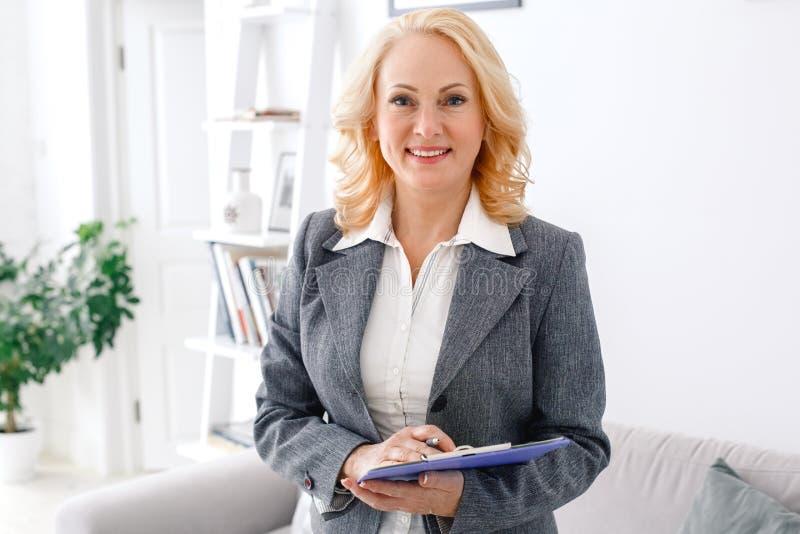 Kobieta psychologa portreta pozycja przy przypadkowym ministerstwem spraw wewnętrznych przygotowywającym brać notatkę zdjęcia stock