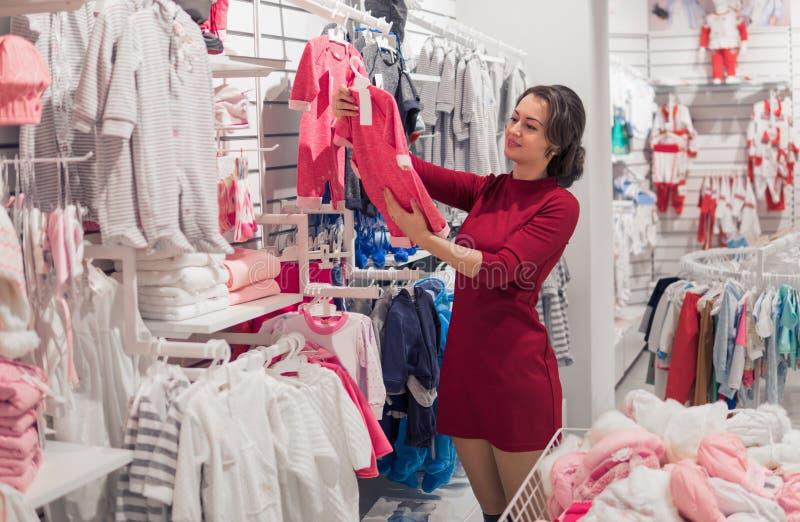 Kobieta, ręczny viewing stojak z dziecka ` s odzieżą w sklepie obrazy stock